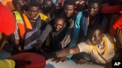 In this Thursday, July 28, 2016 photo, about 150 sub-Saharan refugees and migrants receive life jackets as they aboard an overcrowded rubber boat and wait to be assisted by an NGO during a rescue operation on the Mediterranean Sea, about 23 kilometers (14 miles) north of Sabratha, Lybia.