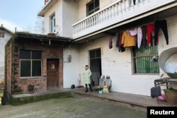 FILE - The wife of silicosis patient Wang Zhaohong stands in front of their house in Sangzhi county, Hunan province, China, Nov. 27, 2018.