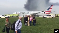 In this photo provided by passenger Jose Castillo, fellow passengers walk away from a burning American Airlines jet that aborted its takeoff and caught fire on the runway at Chicago's O'Hare International Airport, Oct. 28, 2016.