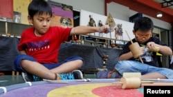 Dua orang anak laki-laki bermain gasing dalam acara permainan tradisional di sebuah sekolah di Jakarta (1/10). (Reuters/Iqro Rinaldi)
