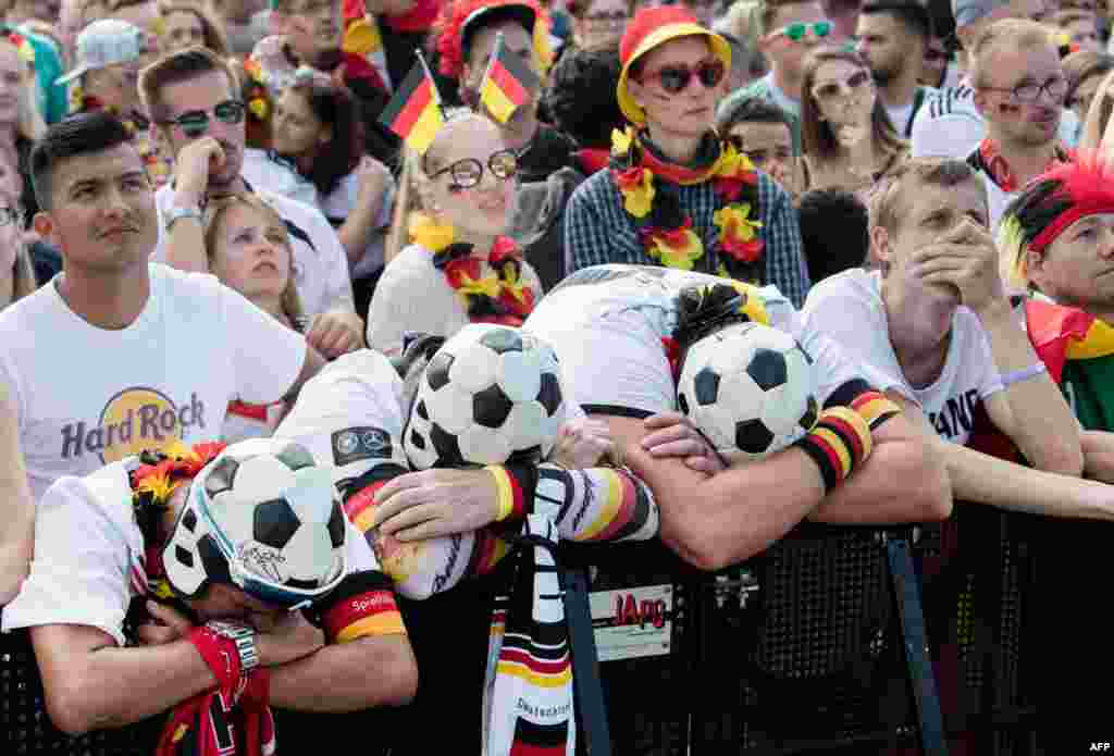 Supporters of the German national football team react as they attend a public viewing event at the Fanmeile in Berlin to watch the 2018 World Cup Group F football match between South Korea and Germany.