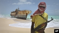 FILE - A masked Somali pirate stands near a Taiwanese fishing vessel that washed up on shore after the pirates were paid a ransom and released the crew, Sept. 23, 2012.