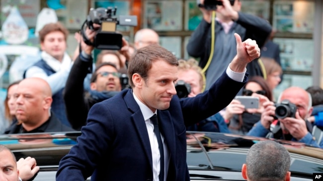 El candidato centrista Emmanuel Macron, saluda después de votar en la primera vuelta de las elecciones presidenciales francesas, en Le Touquet, en el norte de Francia, el domingo 23 de abril de 2017.