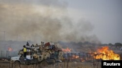 """A truck piled with furniture and other items drives past burning businesses and homesteads, locally known as """"tukuls"""", in the center of Abyei, central Sudan in this handout photograph released on May 28, 2011."""