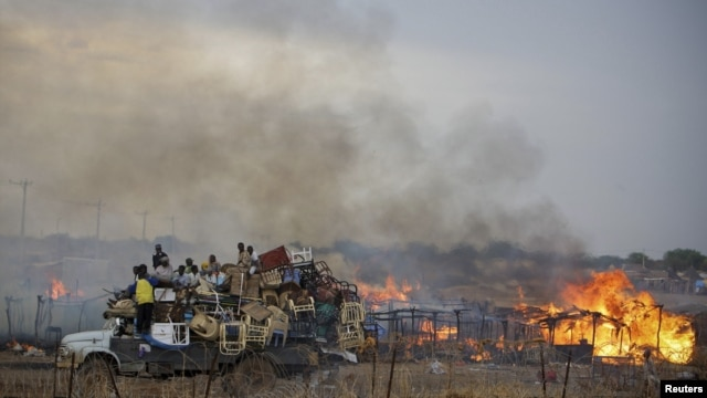 "A truck piled with furniture and other items drives past burning businesses and homesteads, locally known as ""tukuls"", in the center of Abyei, central Sudan in this handout photograph released on May 28, 2011."