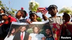 A girl holds a portrait of U.S. President Barack Obama and his family during a rally in front of the U.S Embassy in Phnom Penh, March 17, 2015.