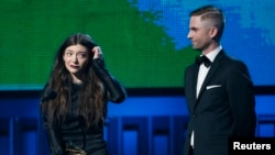 """Lorde is accompanied by producer Joel Little after they won the award for Song of the Year for """"Royals"""" at the 56th annual Grammy Awards in Los Angeles, Jan. 26, 2014."""
