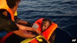 Un migrant d'Erythrée est récupéré de la mer après avoir sauté d'un bateau en bois bondé, à environ 13 milles au nord de Sabratha, Libye, 29 août 2016.