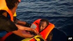 Un migrant en train d'être secouru après une chute dans l'eau de la Méditerranée à Sabratha, Libye, 29 août 2016