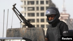 FILE - A policeman stands guard in Karachi, Pakistan, May 14, 2015. Police said Thursday that IS commander Kamran Aslam, also known as Kamran Gujjar, was killed in a raid in Karachi's Ettihad Town neighborhood.
