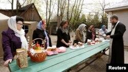"Pendeta Ortodoks Ukraina memercikkan air suci pada umat dan hidangan ""paskha"", sehari sebelum kebaktian Paskah di gereja Ortodoks di Luhansk, sebelah timur Ukraina (19/4). (Reuters/Vasily Fedosenko)"