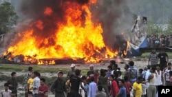 Curiosos observan un avión de Sita Air arder cerca del aeropuerto de Katmandu, en Nepal, el viernes 28 de septiembre de 2012. 19 personas murieron en el accidente.