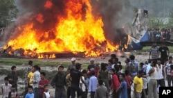 Dân chúng vây quanh chiếc phi cơ đang bốc cháy sau khi rơi xuống