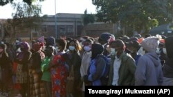 People wait in a queue to be vaccinated at a government hospital in Harare, Zimbabwe on Friday, Sept, 17, 2021. (AP Photo/Tsvangirayi Mukwazhi)