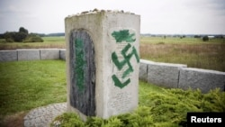 FILE - A monument with Nazi swastikas painted over it is seen in Jedwabne, Poland, Sept. 1, 2011. Polish prosecutors charged three men Tuesday for allegedly propagating Nazism after hidden camera footage of a group celebrating Adolf Hitler's birthday sparked uproar in the country.