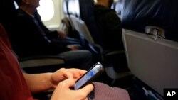 Seorang penumpang pesawat mengecek ponselnya sebelum penerbangan ke Boston.