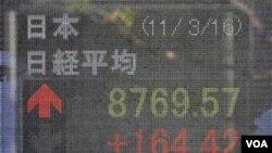 Seorang pria melongok papan indeks saham di jalanan kota Tokyo. Banyak perusahaan di negara ini menunda berbagai kampanye komersial selagi bencana masih menyita perhatian.