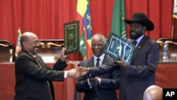 Sudan's President Omar al-Bashir, left, and S. Sudan President Salva Kiir, shake hands on the completion of a signing ceremony in Addis Ababa, Ethiopia, September 27, 2012.