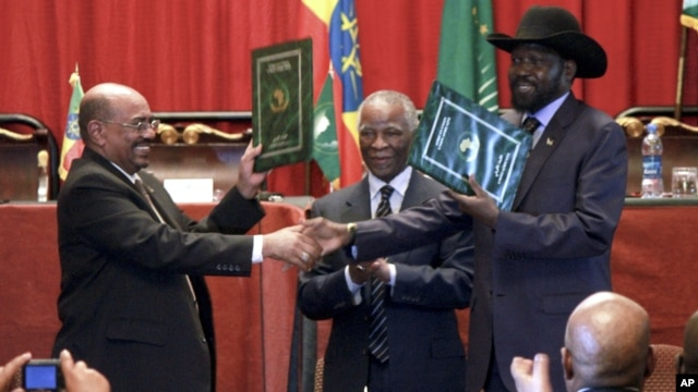 Sudan's President Omar al-Bashir, left, and South Sudan President Salva Kiir, right, shake hands on the completion of a signing ceremony after the two countries reached a deal on economic and security agreements in Addis Ababa, Ethiopia, Sept. 27, 2012.