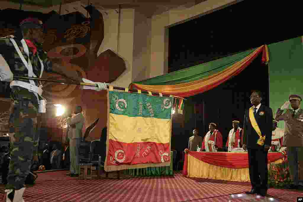 Mali's Interim President Dioncounda Traore, second from right, stands facing a Malian army flag during his swearing in ceremony. (AP)