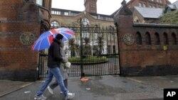 照片中行人步過的一個位於東倫敦的住宅單位﹐英國國防部已經向居民表示會在奧運會期間﹐在屋頂裝置地對空導彈﹐作為奧運的保安設施之一。(資料圖片)