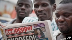 "A Ugandan reads a copy of the ""Red Pepper"" tabloid newspaper in Kampala, Feb. 25, 2014."
