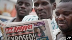 "FILE - A Ugandan reads a copy of the ""Red Pepper"" tabloid newspaper in Kampala, Feb. 25, 2014."