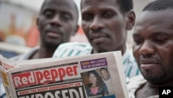 FILE - A Ugandan reads a copy of the Red Pepper tabloid newspaper in Kampala, Feb. 25, 2014.
