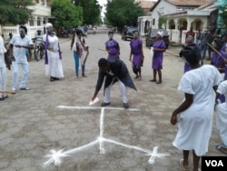 FILE - A man draws a vXCHARXvXCHARX symbol XCHARX common in voodoo, a religion known in Haiti as Vodou XCHARX during a celebration of FXCHARXt Gede in the northeast Haitian city of Fort-Liberte, Nov. 1, 2017. (Jaudelet Junior Saint Vil/VOA)