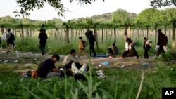 FILE - Afghan migrants rest in the open as others pass by after crossing illegally into Macedonia from Greece, near the town of Gevgelija, Macedonia, May 6, 2015.