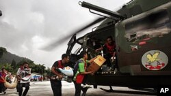 Volunteers carry relief materials to an Indian air force helicopter to airdrop in quake-hit remote villages in Mangan, India, September 22, 2011.