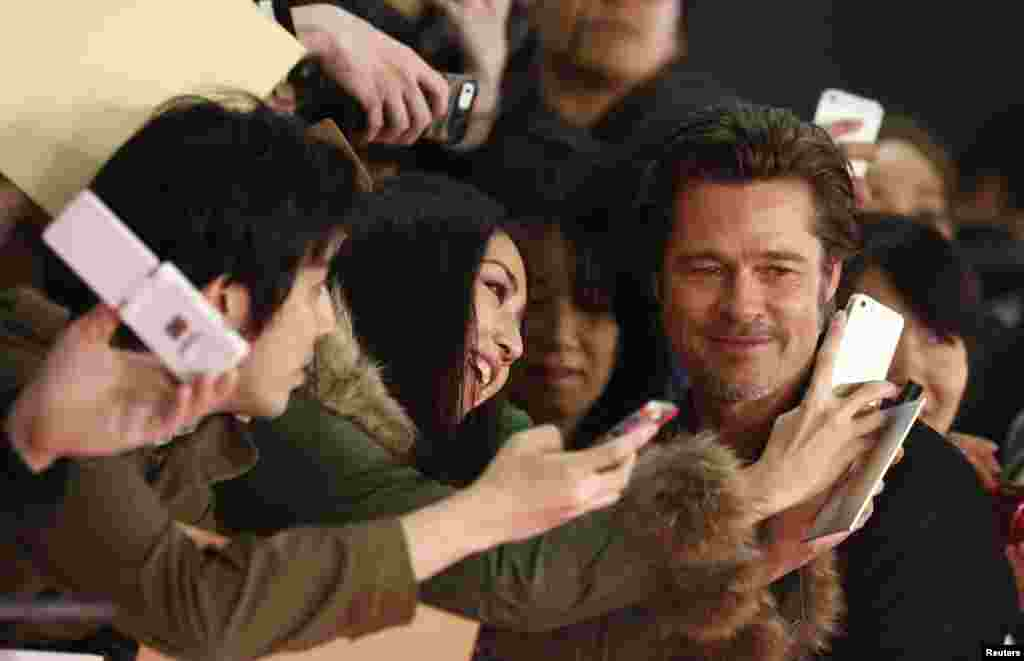 """Cast member Brad Pitt takes pictures with fans as he promotes the movie """"Fury"""" in Tokyo, Japan, Nov. 15, 2014."""
