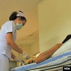 Seorang perawat di Thailand memberika obat anti-retrovirus kepada seorang pasien HIV.