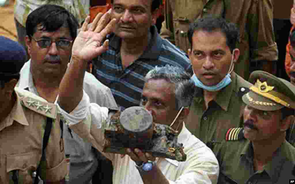 """A Director General of Civil Aviation (DGCA) official (C) holds up an aircraft part which officials claim is the """"black box"""" of the doomed Air India Express flight 812, discovered at the crash site in Mangalore on May 25, 2010. Investigators recovered May"""