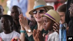 FILE - Madonna claps hands with her daughter Mercy, right, in Kasungu, about 150 kilometers north of the capital Lilongwe, Nov. 30, 2014.