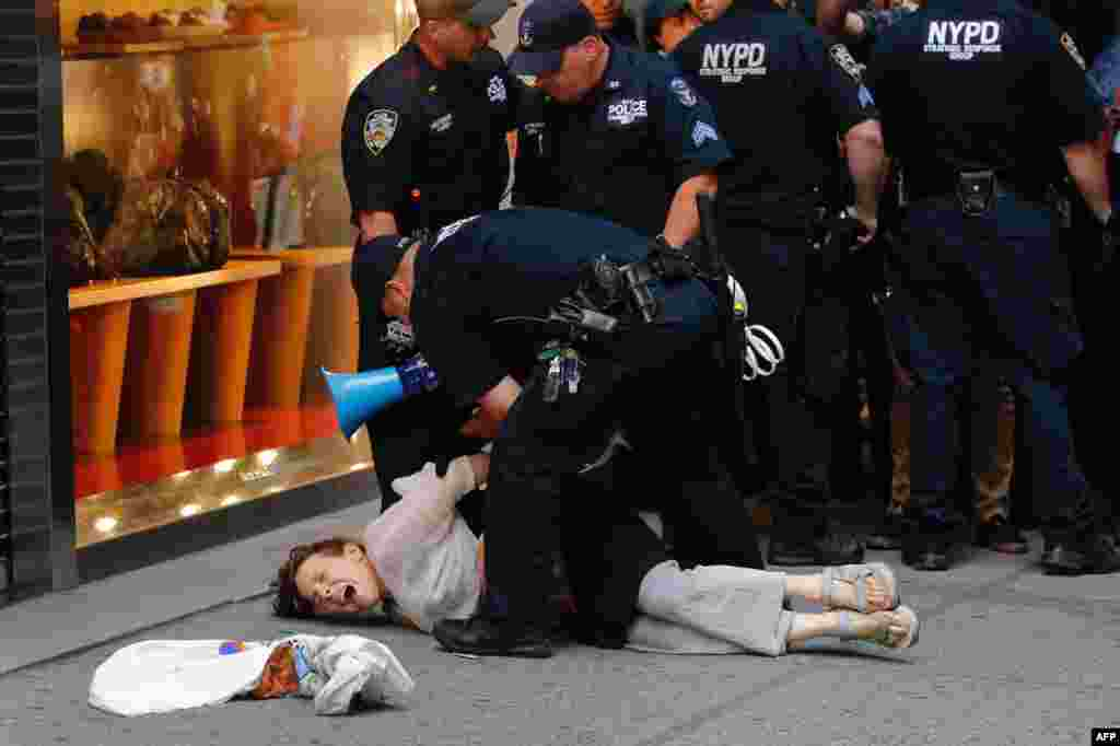 Police arrest a woman near Trump Tower during a protest against U.S. President Donald Trump in New York, Aug. 14, 2017.