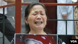 Zheng Shuzhen, seorang nenek di Tiongkok memegang foto cucunya yang meninggal setelah minum susu yang tercemar.