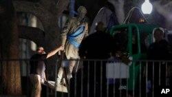 """Sebuah patung Pemimpin Konfederasi, Jenderal Robert E. Lee dipindahkan dari kampus Universitas Texas di kota Austin, Senin (21/8). Rektor Universitas Texas memerintahkan disingkirkannya patung-patung pemimpin Konfederasi dari lingkungan kampus karena menurutnya hal itu merupakan simbol """"supremasi kulit putih dan Neo-Nazi"""" modern."""