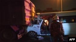 Para petugas dari Dinas Pemadam Kebakaran dan SAR Malaysia sedang bekerja di lokasi kecelakaan lalu lintas yang menewaskan seorang supir dan mencederai empat pebulu tangkis, termasuk pebulu tangkis nomor satu dunia, Kento Momota, di jalan tol menuju Banda