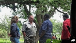 Gary Stafford and his wife talk to the Director General of National Parks, Vitalis Chadenga, after their bird sanctuary Kuimba Shiri Safari Lodge was besieged by scores of Zanu PF supporters demanding they leave, on Lake Chibero, Zimbabwe, January 22, 201