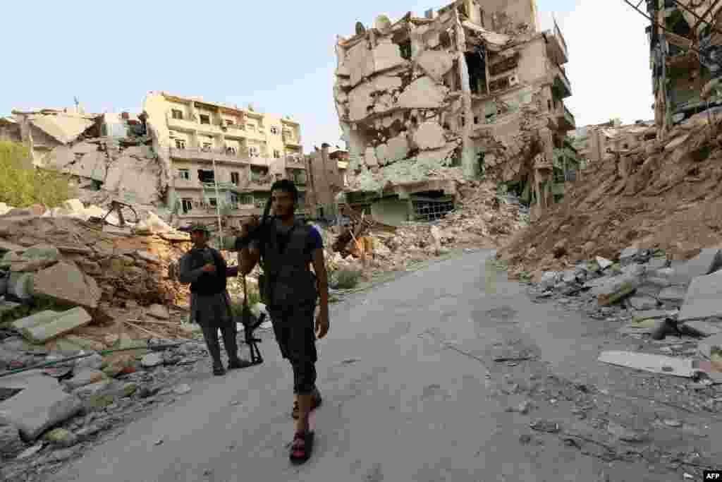 Rebel fighters walk in front of damaged buildings in Karam al-Jabal neighborhood of Aleppo, Syria.