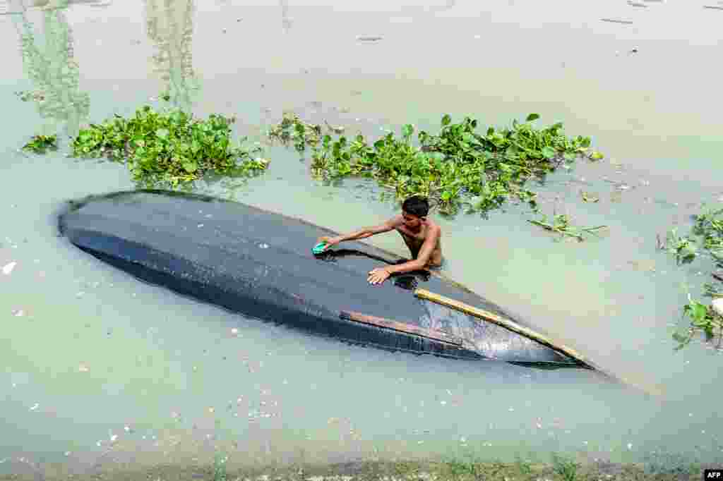A man cleans his boat in Buriganga River in Dhaka, Bangladesh.