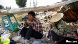 在北京郊区拆毁的建筑物废墟捡垃圾的两位民工吃午饭(2017年10月1日)