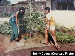 Sonny Duong and his sister, Co Tong with plants in their garden in California with seeds their father brought from Vietnam.