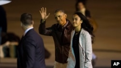 President Barack Obama waves as he heads toward Air Force One, accompanied by his daughter Malia, at the international airport serving Buenos Aires, Argentina, March 25, 2016.