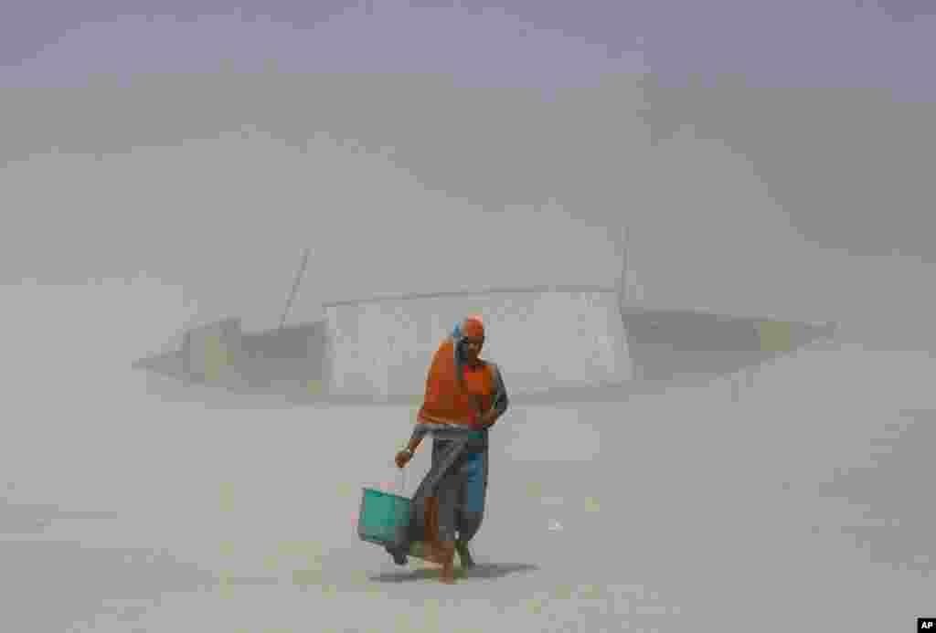 인도 가우하티의 브라마푸트라 강 인근에서 한 여성이 모래바람을 맞으며 물을 길어오고 있다. 연례 '물의 날'을 하루 앞두고 세계 곳곳에서는 다음 세대를 위한 물 자원 절약과 관리를 강조하고 있다.