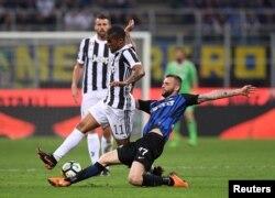 지난 5월 이탈리아 밀란의 경기장에서 유벤투스의 도글라스 코스타(왼쪽)와 인터 밀란의 마르셀로 브로조비치가 공을 두고 몸싸움을 벌이고 있다.