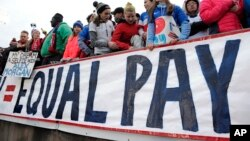 FILE - Fans stand behind a large sign for equal pay for the women's soccer team during a match between the United States and Colombia in East Hartford, Conn. The World Economic Forum's annual Global Gender Gap Report released on Oct. 25, 2016, found that the global gender pay gap will not be closed for another 170 years if current trends continue.