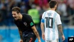 Fudbaler Argentine Lionel Mesi odlazi sa terena posle ubedljivog poraza od Hrvatske, dok se hrvatski reprezentativac Sime Vrsaljko raduje (Foto: AP/Pavel Golovkin)