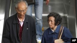 An elderly couple hold their grandson's hands as they enter a subway station in People's Square, Shanghai April 28, 2011.